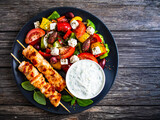 Fried souvlaki, greek salad and tzatziki on wooden table