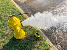 Top View Yellow Fire Hydrant Gushing Water Across A Residential Street Near Dallas, Texas, USA
