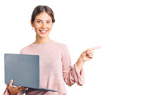 Beautiful Caucasian Woman With Blonde Hair Working Using Computer Laptop Smiling Happy Pointing With Hand And Finger To The Side