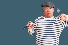 Senior Handsome Grey-haired Man Holding Golf Club And Ball With Angry Face, Negative Sign Showing Dislike With Thumbs Down, Rejection Concept