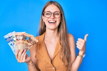 Young Blonde Girl Holding Canadian Dollars Smiling And Laughing Hard Out Loud Because Funny Crazy Joke.