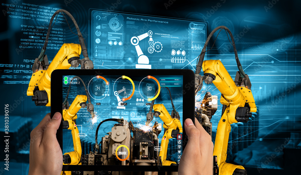 Fototapeta Engineer controls robotic arms by augmented reality industry technology application software. Smart robot machine in future factory working in concept of Industry 4.0 or 4th industrial revolution.