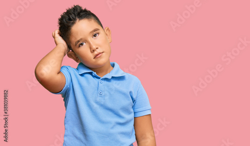 Fototapeta Little boy hispanic kid wearing casual clothes confuse and wondering about question