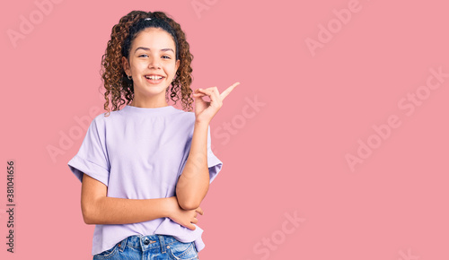 Obraz Beautiful kid girl with curly hair wearing casual clothes with a big smile on face, pointing with hand and finger to the side looking at the camera. - fototapety do salonu
