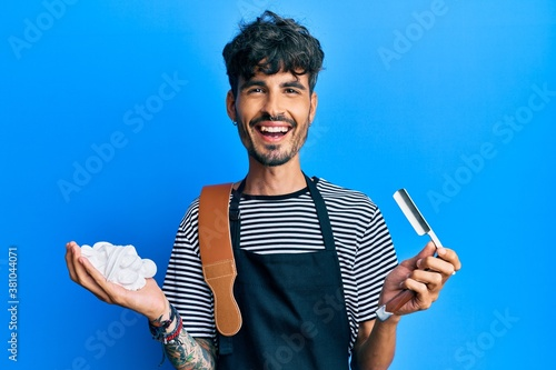 Obraz na plátně Young hispanic man wearing barber apron holding razor and foam smiling and laughing hard out loud because funny crazy joke