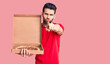 canvas print picture Young handsome man with beard holding delivery cardoboard with italian pizza pointing with finger to the camera and to you, confident gesture looking serious