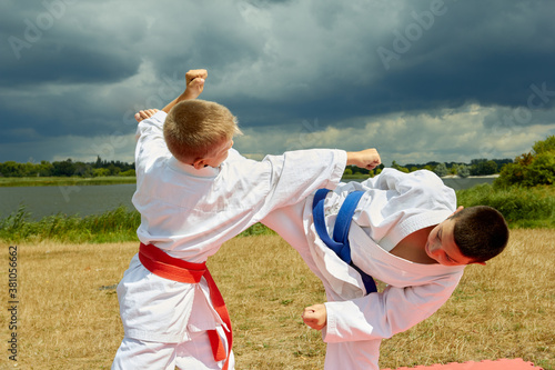 Obraz na plátně Athletes on the background of nature with a red and blue belt perform punches an