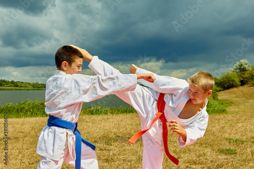 Fototapeta Two athletes on the background of nature with a red and blue belt perform punche