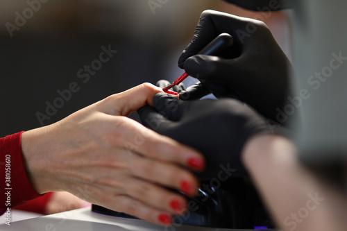 Fototapeta Manicurist paints the nails red. Manicure master training concept obraz