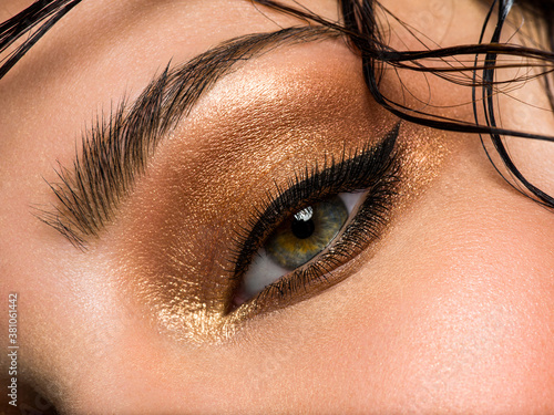 Fotografía close up of beautiful female eye with a brown makeup