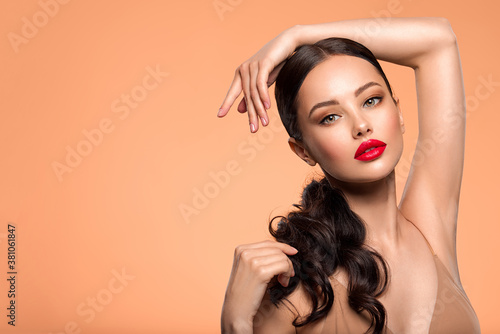 Fototapeta Beautiful white girl with a red lipstick on lips. Stunning brunette girl with long hair tail.  Closeup face of young beautiful woman with a healthy clean skin. Pretty woman with bright makeup obraz