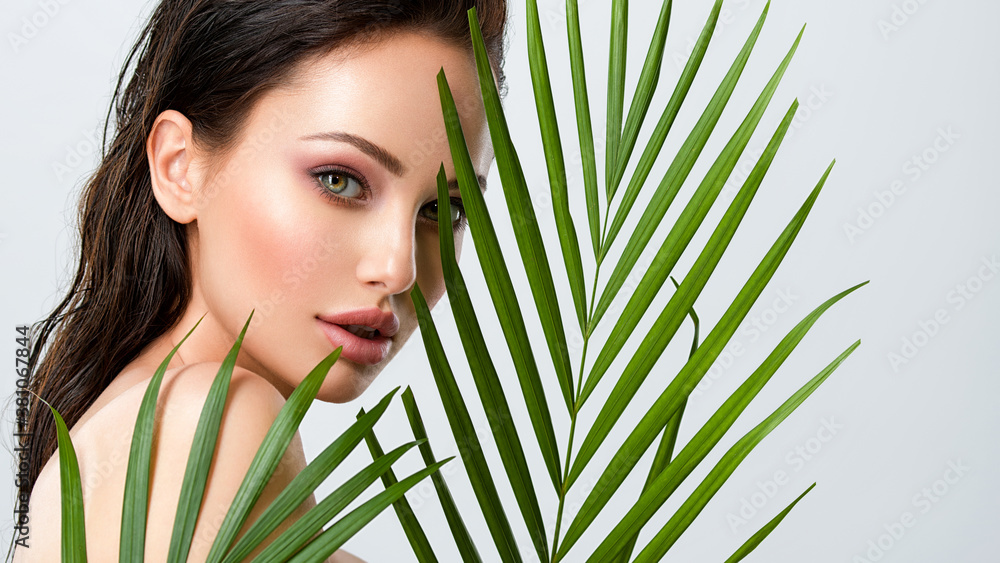 Fototapeta Young beautiful woman with healthy skin of face and palm leaves. Closeup fresh face of an attractive caucasian girl with green plants. Model with bright brown eye makeup. Skin care concept.