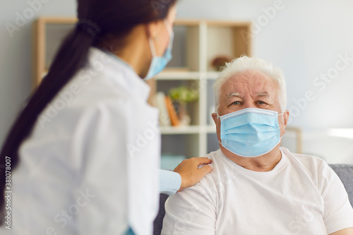 Leinwand Poster Woman doctor visits the elderly man and provides him with support during the quarantine