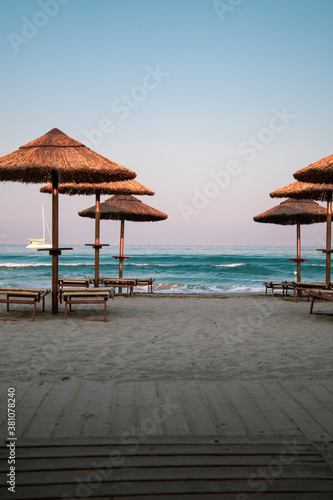 Obraz Beautiful dusk and blue hour light just after sunset in a beach club in Villasimius, Sardinia, italy. Straw sub umbrellas and wooden sunbeds, soft pink sky, summer magic atmoshpere. - fototapety do salonu