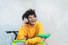 Happy Afro Man Listening To Playlist Music With Wireless Headphones Outdoor