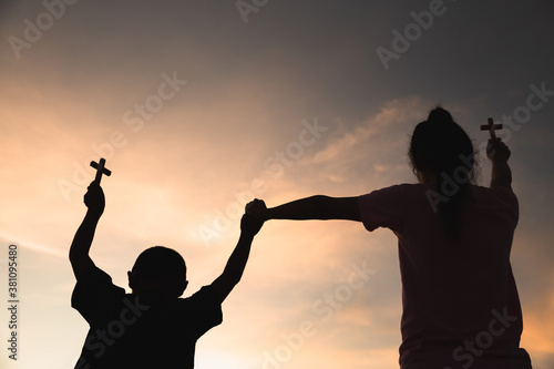 Fotografía Silhouette off hands holding wooden cross  on sunrise background, Crucifix, Symbol of Faith
