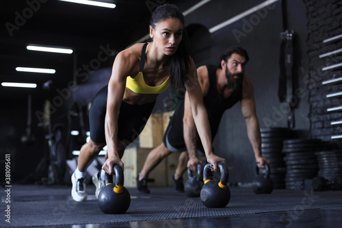 Sporty indian man and woman doing push-up in a gym.