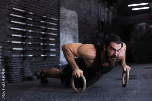 Sporty indian strong man doing push-ups on rings.