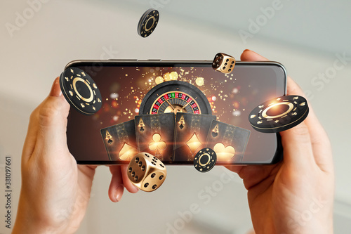 Fototapeta Creative background, online casino, in a man's hand a smartphone with playing cards, roulette and chips, black-gold background. Internet gambling concept. Copy space obraz