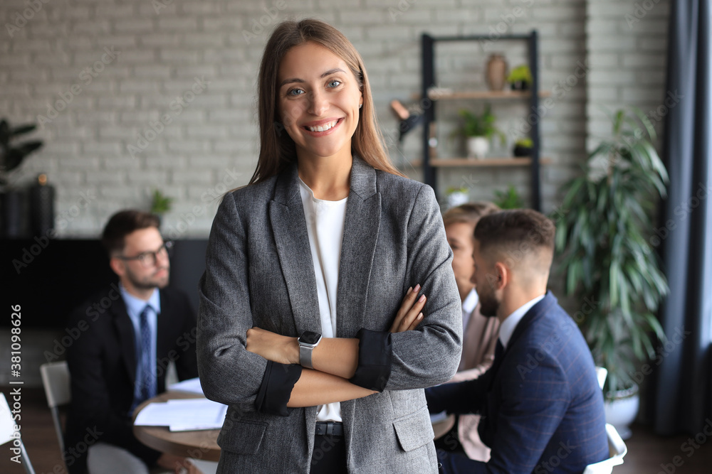 Fototapeta Business woman with her staff, people group in background at modern bright office indoors.