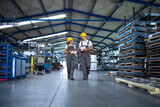 Factory workers in work wear and yellow helmets walking through industrial production hall and discussing about delivery deadline.