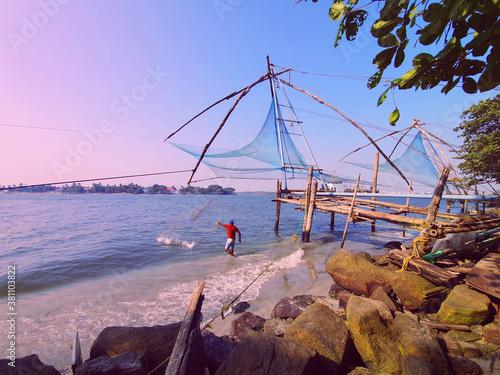 Canvastavla Indian fisherman fishing with net near the sea on evening near the Chinese fishing nets at the Fort Kochi beach, Kerala India