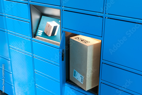 Obraz na plátne Close up Of Light Blue Self-Service Post Terminal Machine With Touchscreen Monitor and Open Locker With Parcel Inside
