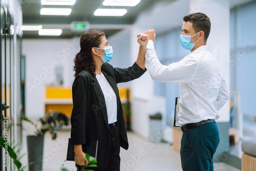 Fototapeta Portrait of two colleagues wearing face masks bumping elbows while greeting each other at work in office. Teamwork during pandemic in quarantine city. Covid-19.  obraz