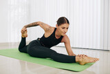 Fit young woman doing side splits and bending forward to her right leg