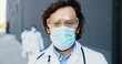 Portrait of Caucasian good-looking man doctor in medical mask, goggles and with stethoscope looking at camera. Close up male physician in respiratory protection. Multi ethnic doctors on background.
