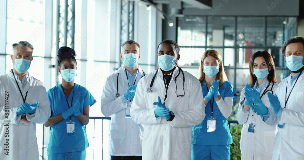 Fototapeta Mixed-races team of male and female doctors applauding in hospital. International group of medics in medical masks. Protected workers. Multi ethnic physicians and nurses in uniforms in clinic Applause
