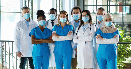 Fototapeta Mixed-races busy team of male and female doctors posing to camera and crossing hands in hospital. International group of medics in medical masks. Protected multi ethnic physicians and nurses in clinic obraz