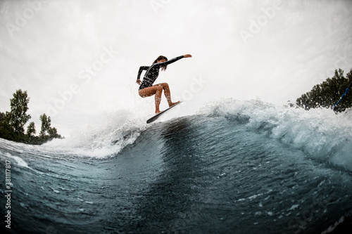 Leinwand Poster young sports woman surfs coolly on surf board and jumps on the wave