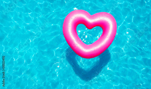 Obraz na plátně Inflatable rose heart buoy swim in the swimming pool view from above