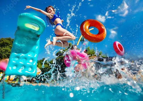 Girl in a group of teenage children have fun in the swimming pool diving with inflatable toys doughnuts, matrass jump and splash in the water
