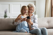 Look here, my darling. Senior grandma and small girl grandkid spending time together using phone, texting message, chatting, dialing number, watching funny photos in social network, browsing internet