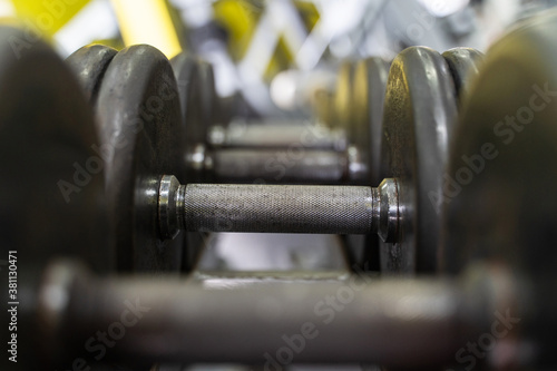 Foto Close up on row of dumbbells in the rack in gym - selective focus background - d