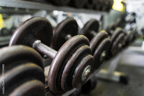 Close up on row of dumbbells in the rack in gym - selective focus background - d Fotobehang
