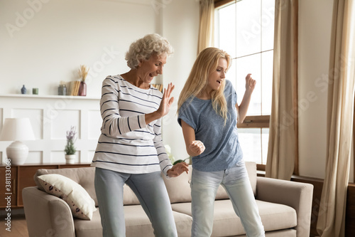 Improvised party. Elder and younger women best friends, aged active granny and grown grandchild girl spending time together dancing relaxing at home celebrating housewarming, purchasing new apartment