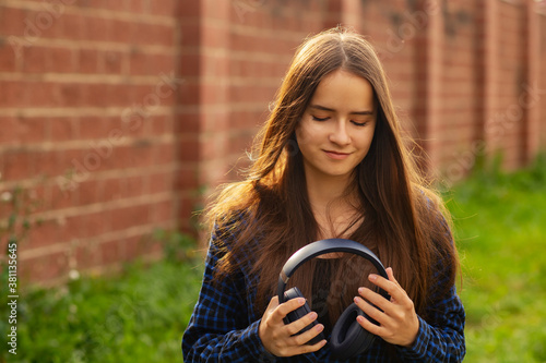 Photo portrait of a happy girl in wireless headphones in summer on a city street on a