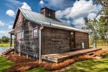 Scenic View Of The Rear Exterior Of A Rural Rustic Wooden Camp House Used For Fishing And Hunting. The House Is Located On A Large Pond