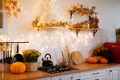 Fototapeta Autumn kitchen interior. Red and yellow leaves and flowers in the vase and pumpkin on light background obraz