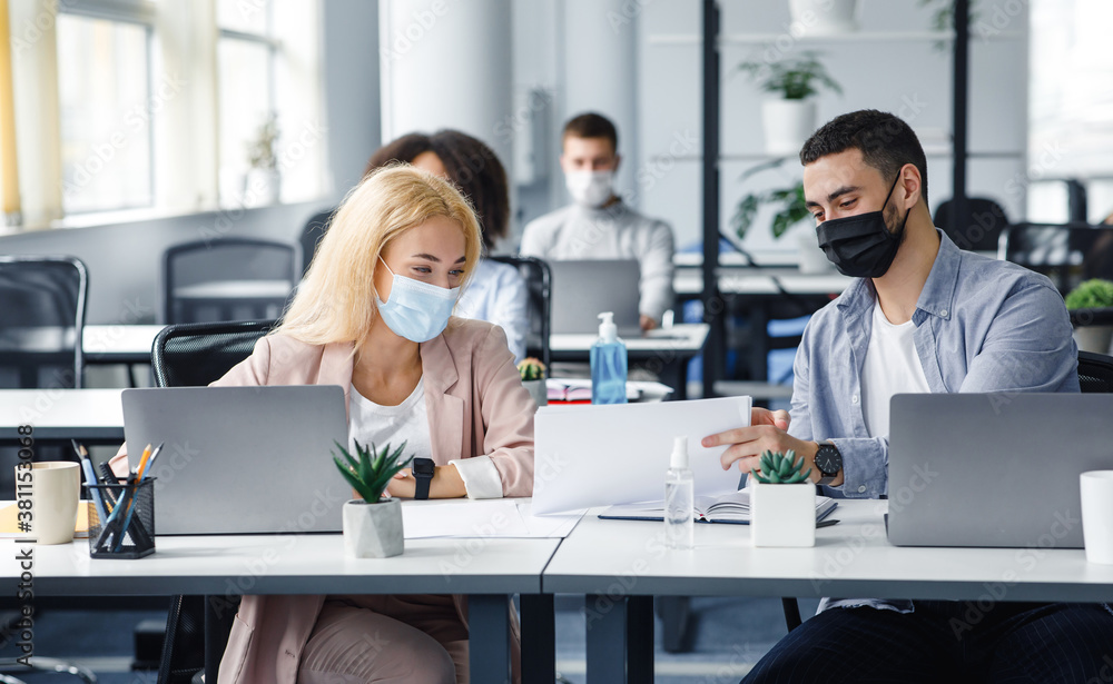 Fototapeta Social distance and work with documents in modern office. Millennial man and woman with papers in workplace with laptops and bottle of antiseptic talk after quarantine