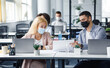 Social distance and work with documents in modern office. Millennial man and woman with papers in workplace with laptops and bottle of antiseptic talk after quarantine