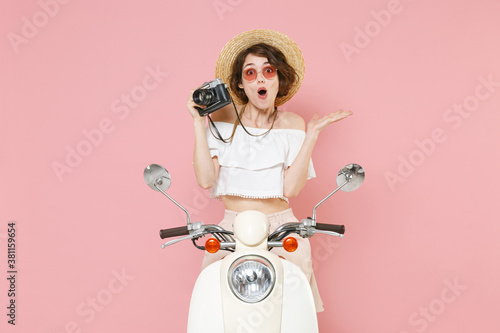 Shocked young brunette woman 20s wearing white summer clothes hat eyeglasses hold in hand retro vintage photo camera sitting driving moped isolated on pastel pink colour background studio portrait.