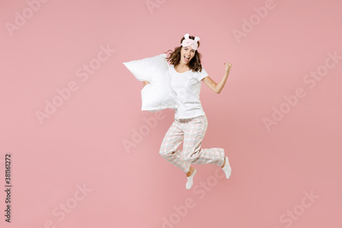 Obraz Full length portrait of happy young woman in white pajamas home wear jumping hold pillow doing winner gesture rest at home isolated on pastel pink background studio. Relax good mood lifestyle concept. - fototapety do salonu