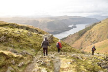 Three People Trekking Together Down A Path In Helvelln Lake Dsitrict