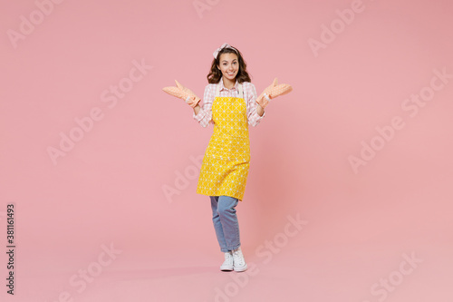 Slika na platnu Full length portrait of smiling young brunette woman housewife in yellow apron gloves potholders spreading hands doing housework isolated on pastel pink colour background studio