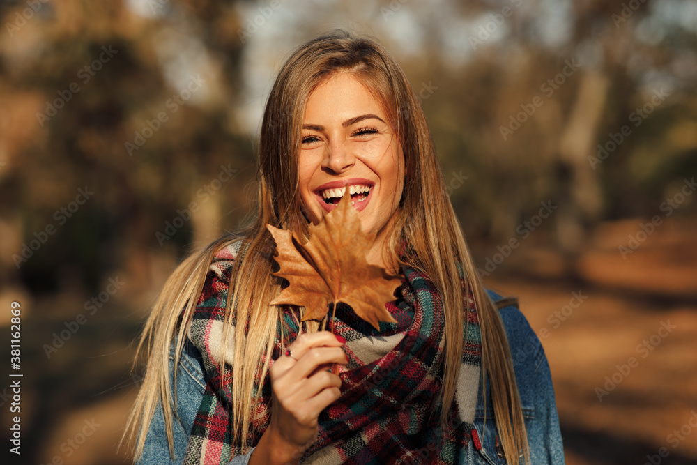 Fototapeta Portrait of a beautiful blonde with a smile on face holding a leaf in hand in the park