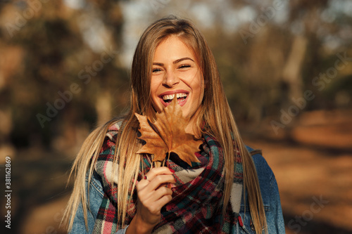 Fotografía Portrait of a beautiful blonde with a smile on face holding a leaf in hand in th